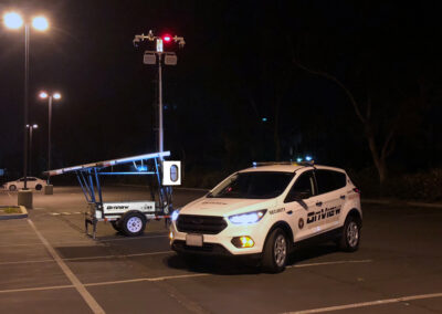 Solar security trailer and security patrol vehicle in a parking lot